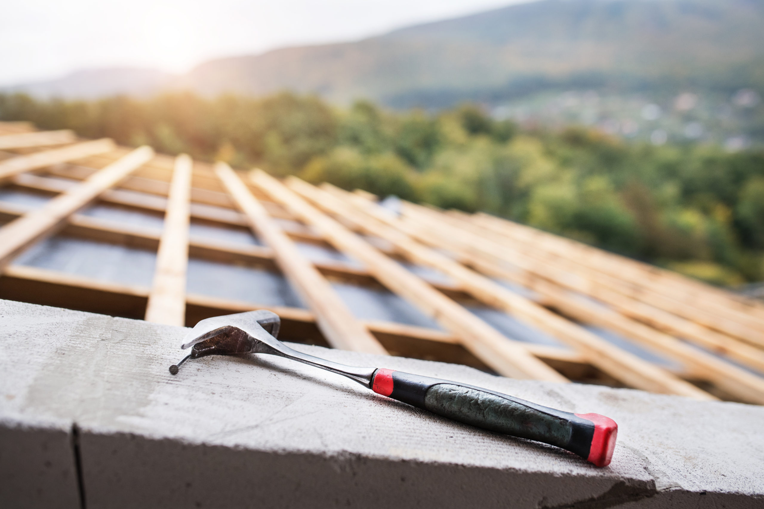 Hammer on the roof on the construction site. House construction.